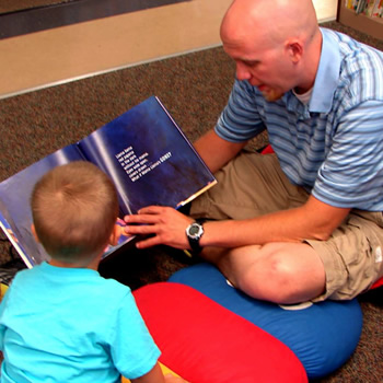 Dad reading to child at the library